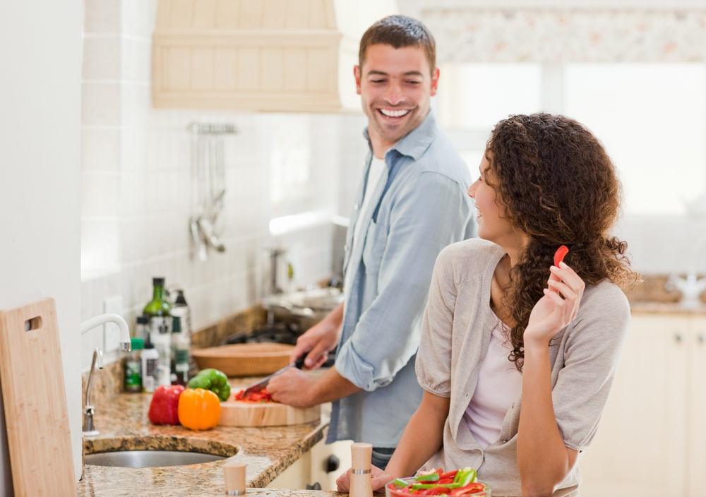 Beautiful woman looking at her husband who is cooking at home-1
